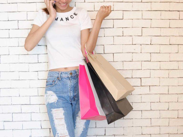 Facebook Audience Insights - Frau an einer Wand mit 3 Shopping Taschen