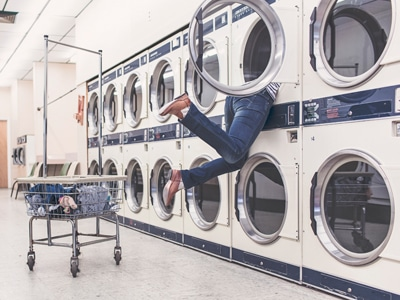 Frau klettert in Waschmaschine